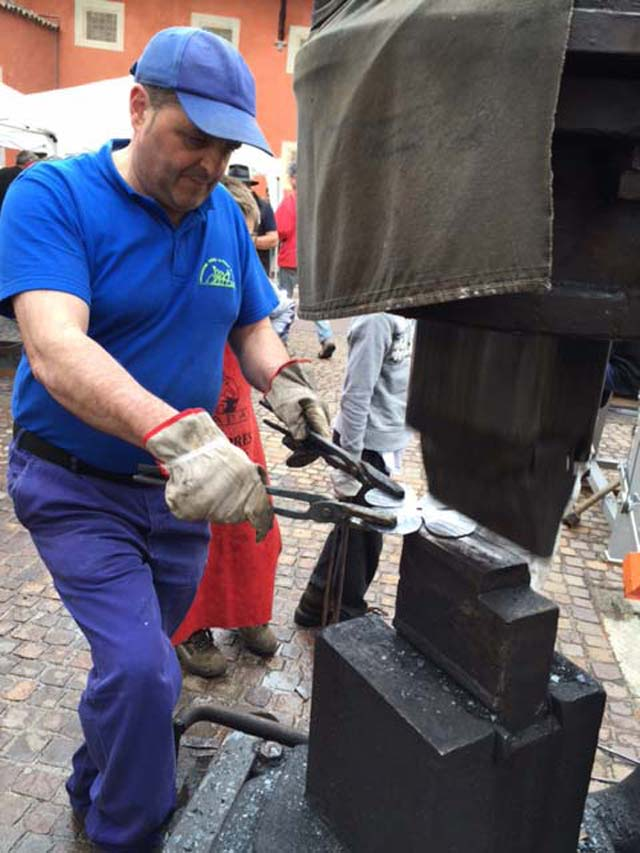 Comenso also known as 'The Magician' a blacksmith from Bienno forging poppies in the square Bienno Italy